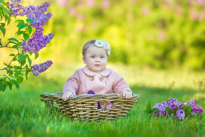 Glimlachend babymeisje 1-2 éénjarigen die bloemkroon dragen, die boeket van sering in openlucht houden het bekijken camera de tij stock foto's