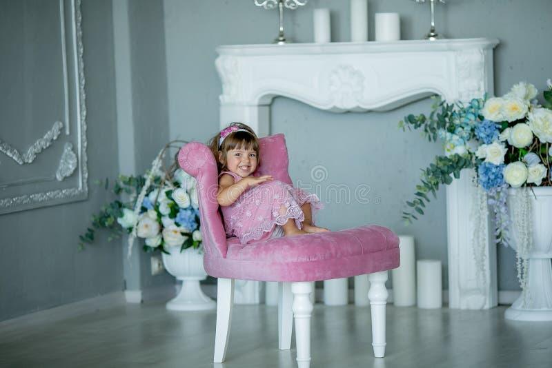 Glimlachend babymeisje die onder 1 éénjarige modieuze kleren dragen die als uitstekende voorzitter over witte open haard in ruimt royalty-vrije stock afbeeldingen