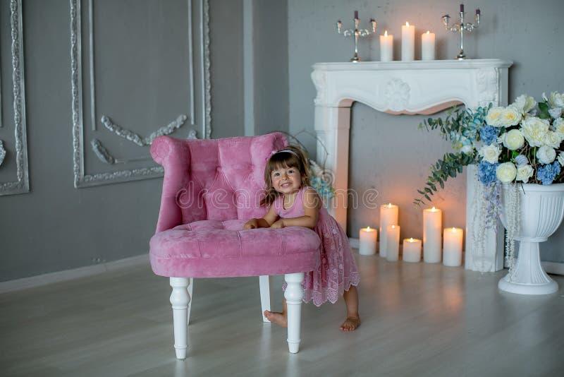 Glimlachend babymeisje die onder 1 ??njarige modieuze kleren dragen die als uitstekende voorzitter over witte open haard in ruimt royalty-vrije stock afbeeldingen