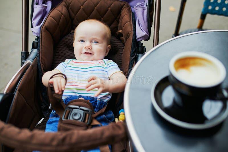 Glimlachend babymeisje in wandelwagen dichtbij de lijst van openluchtkoffie stock fotografie