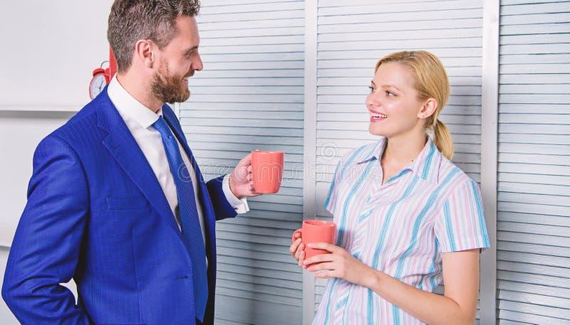 Glimlachend bedrijfspaar bij bureauruimte die in koffiepauze spreken Zaken en mensenconcept Het werkcultuur stock fotografie