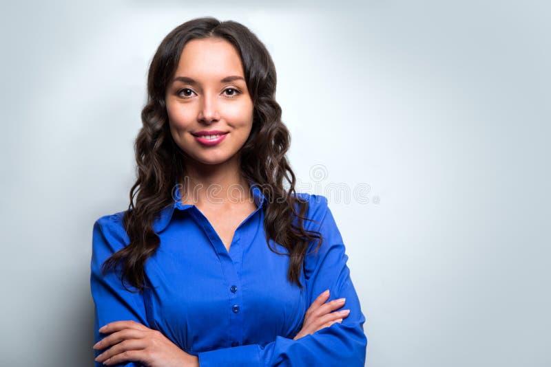 Glimlachend bedrijfsvrouwen blauw kostuum gekleed status tegen wit stock afbeelding