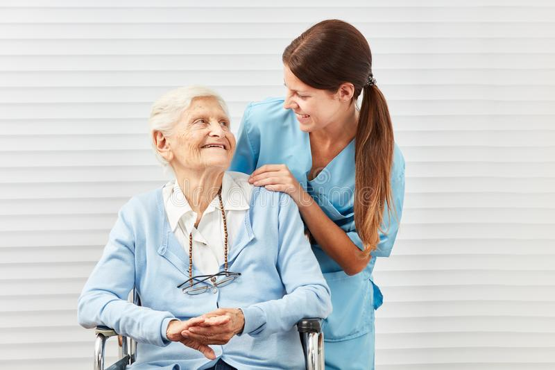 Glimlachend bejaarde in rolstoel en verpleegster royalty-vrije stock foto