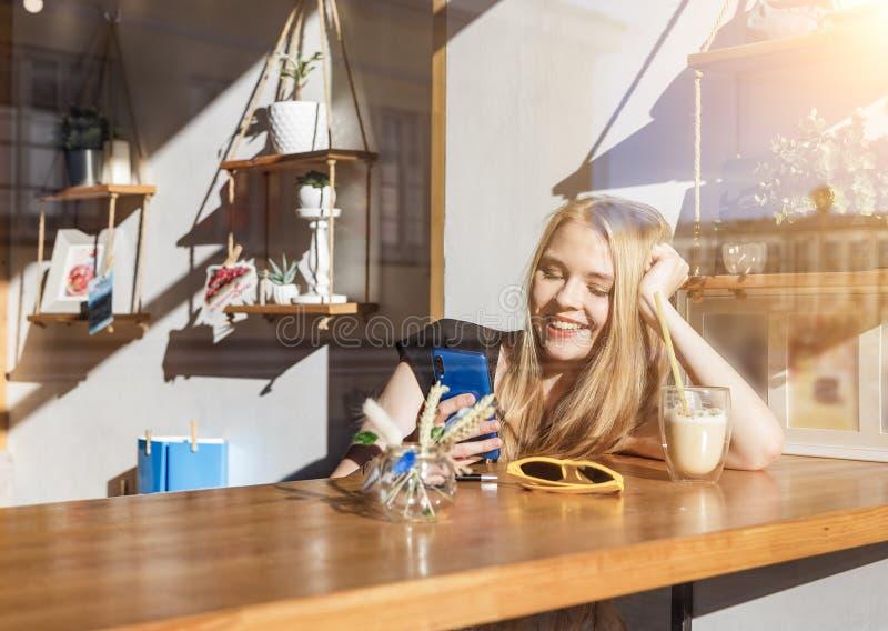 Glimlachend blond meisje die sociaal netwerk babbelen terwijl rust in koffie stock fotografie
