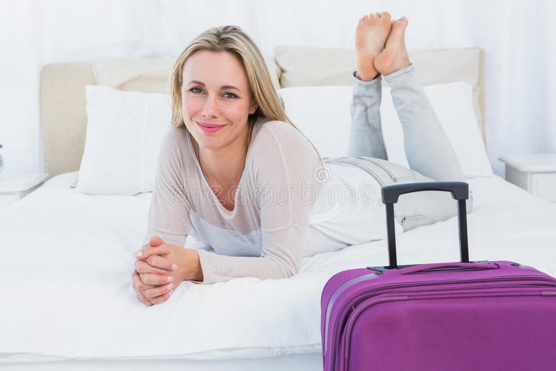 Glimlachend blonde die op het bed dichtbij haar bagage liggen royalty-vrije stock afbeelding