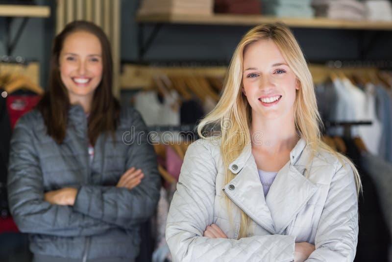 Glimlachend blonde met gekruiste wapens het bekijken camera met erachter vriend stock afbeeldingen