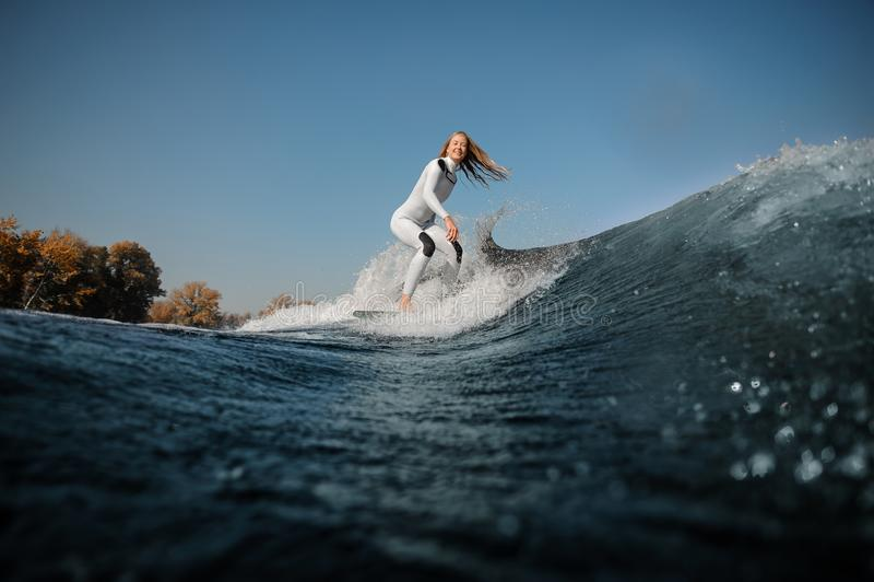 Glimlachend blondemeisje die op wakeboard op de buigende knieën berijden stock afbeeldingen