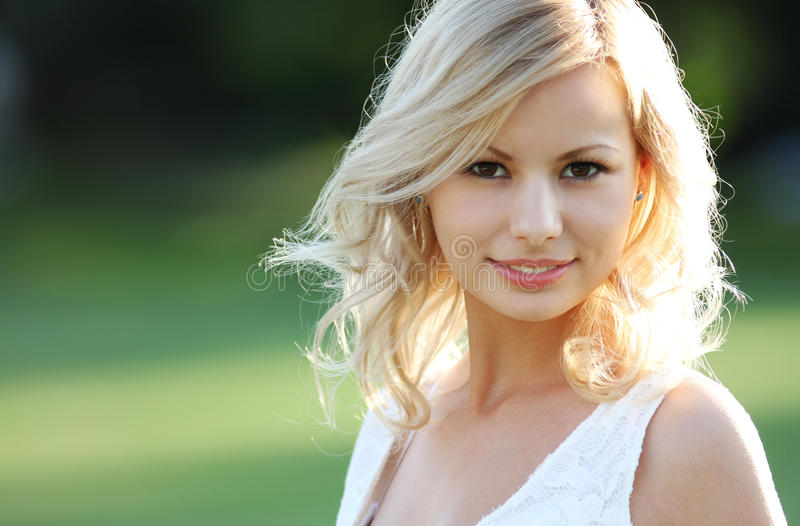 Glimlachend blondemeisje. Portret van gelukkige vrolijke mooie jonge vrouw, in openlucht. stock afbeelding