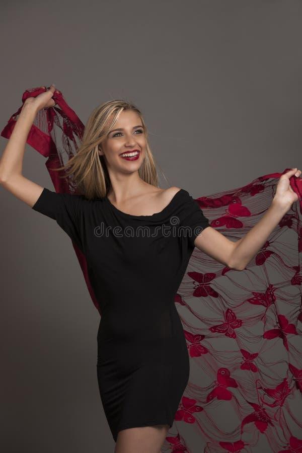 Glimlachend blondemeisje in zwarte kleding met rode vlindersjaal royalty-vrije stock afbeelding