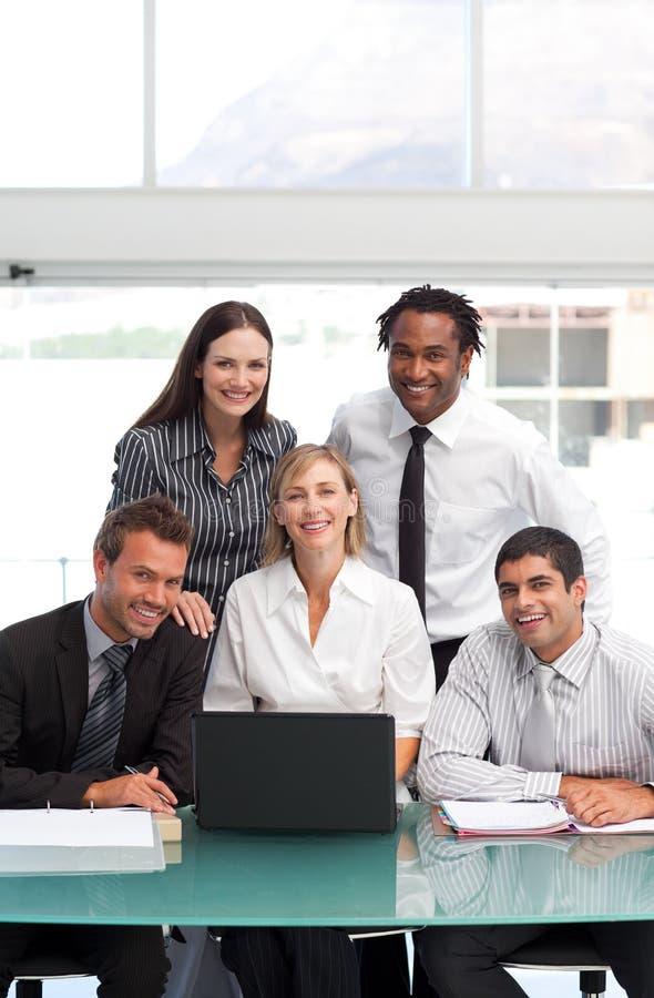 Glimlachend commercieel team dat samen met een lapt werkt royalty-vrije stock afbeelding
