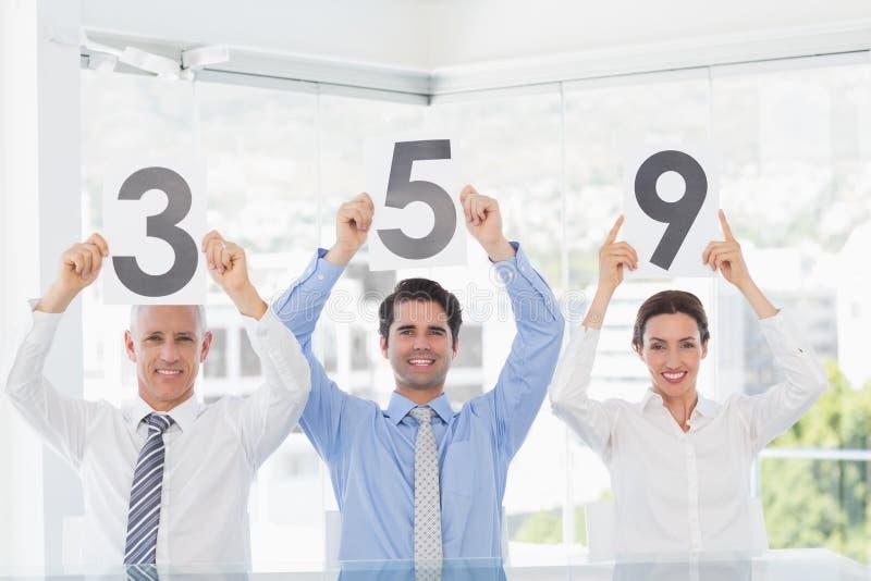 Glimlachend commercieel team die document met classificatie tonen stock foto