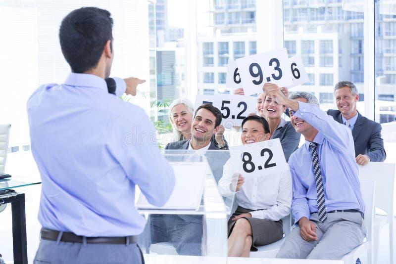 Glimlachend commercieel team die document met classificatie tonen stock afbeelding