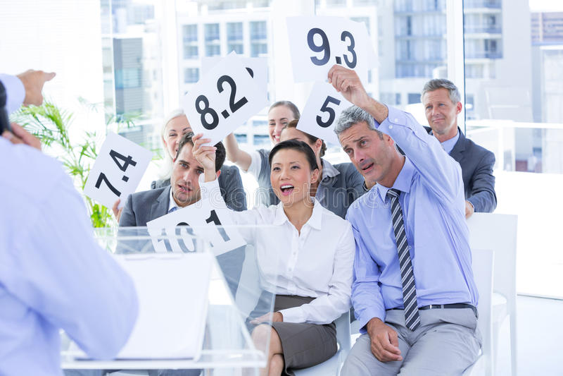Glimlachend commercieel team die document met classificatie tonen royalty-vrije stock afbeelding