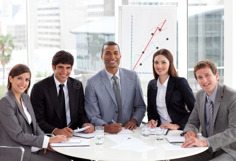Glimlachend commercieel team in een vergadering stock fotografie