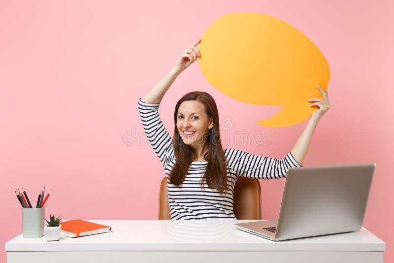 Glimlachend de gele lege spatie van de vrouwengreep zeg het de bellenwerk van de wolkentoespraak bij wit die bureau met PC-laptop royalty-vrije stock afbeelding