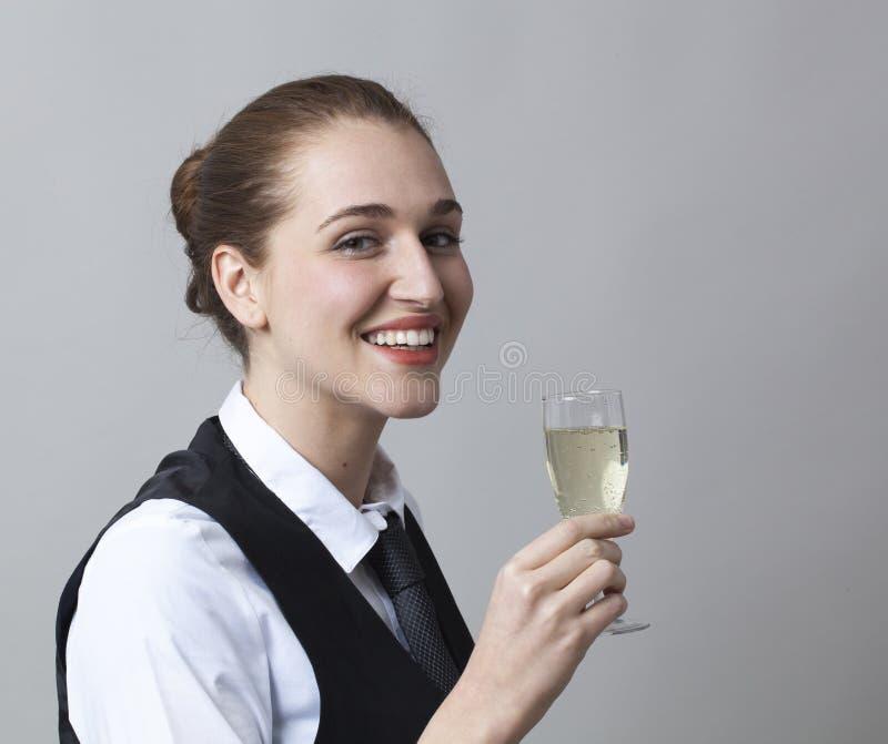 Glimlachend de holdingsglas van het jaren '20meisje bruisende wijn bij partij om succes bij meer sommelier het worden te vieren stock afbeeldingen