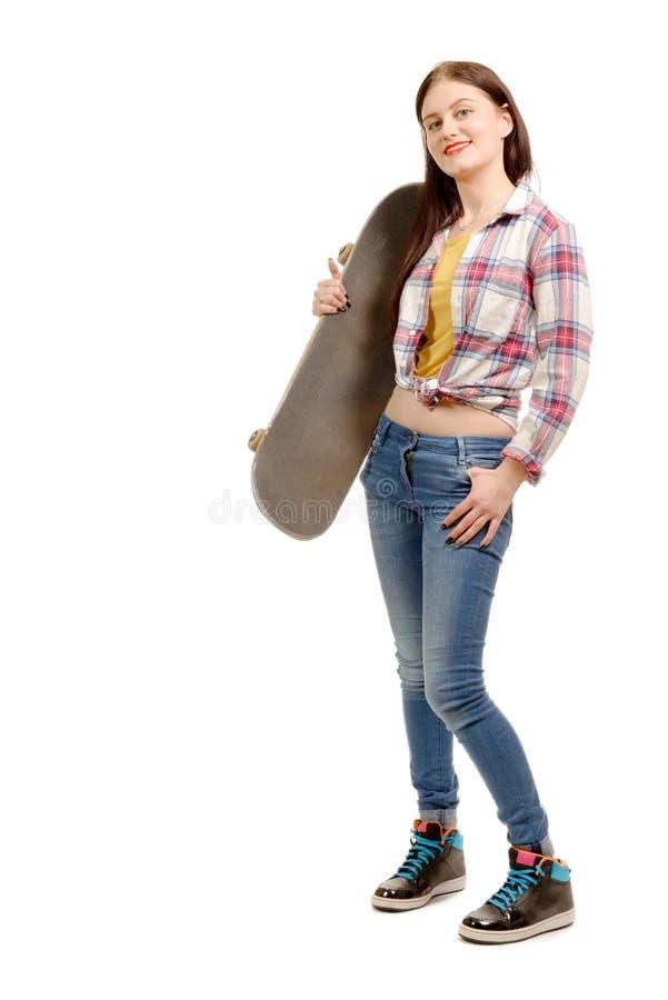 Glimlachend de holdingsskateboard van het schaatsermeisje stock foto