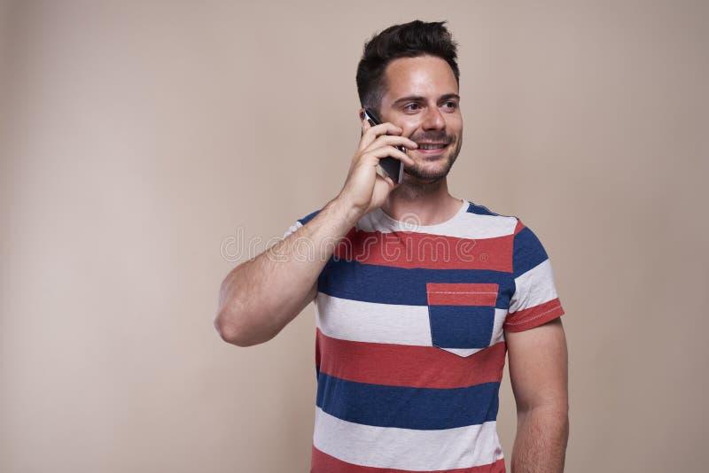 Glimlachend, is de jonge mens op de telefoon stock foto