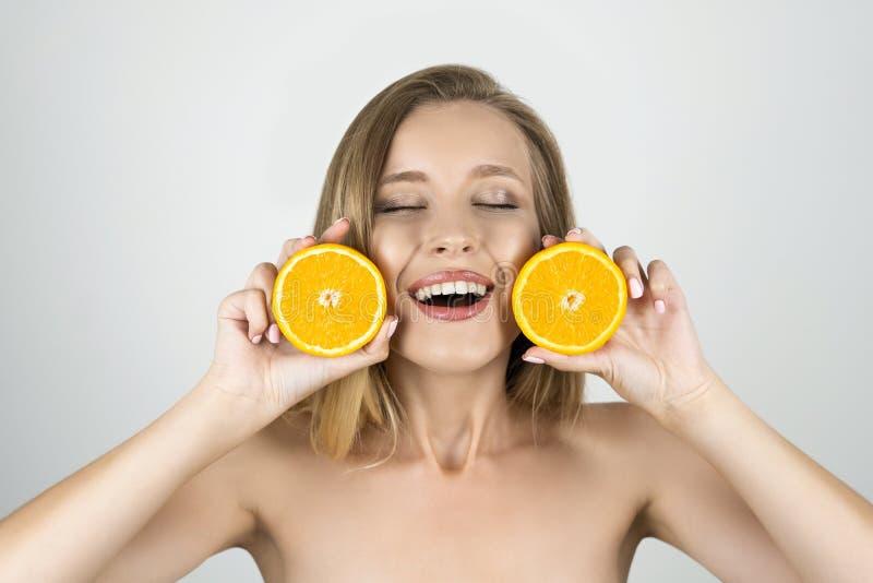 Glimlachend de jonge mooie blonde sinaasappelen van de vrouwenholding in haar handen die tevreden geïsoleerde witte achtergrond k royalty-vrije stock foto