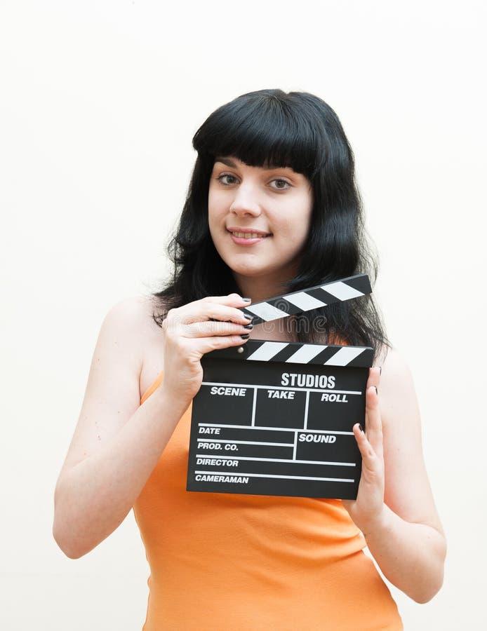 Glimlachend donkerbruin meisje die klep op witte achtergrond tonen royalty-vrije stock foto's