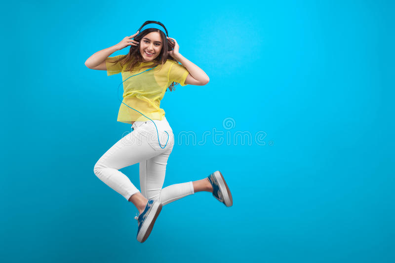 Glimlachend donkerbruin meisje in hoofdtelefoons het springen stock foto