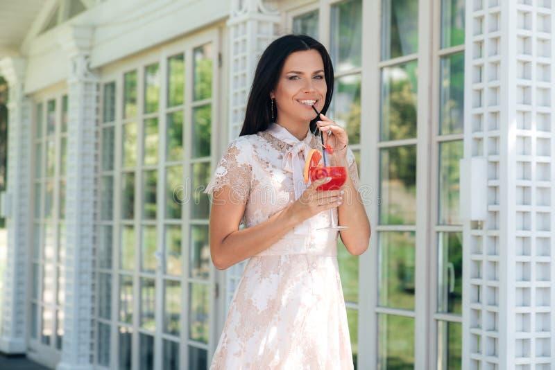 Glimlachend donkerbruin meisje met glas van limonade het stellen in beige kleurenkleding buiten koffie dichtbij een houten en gla stock foto