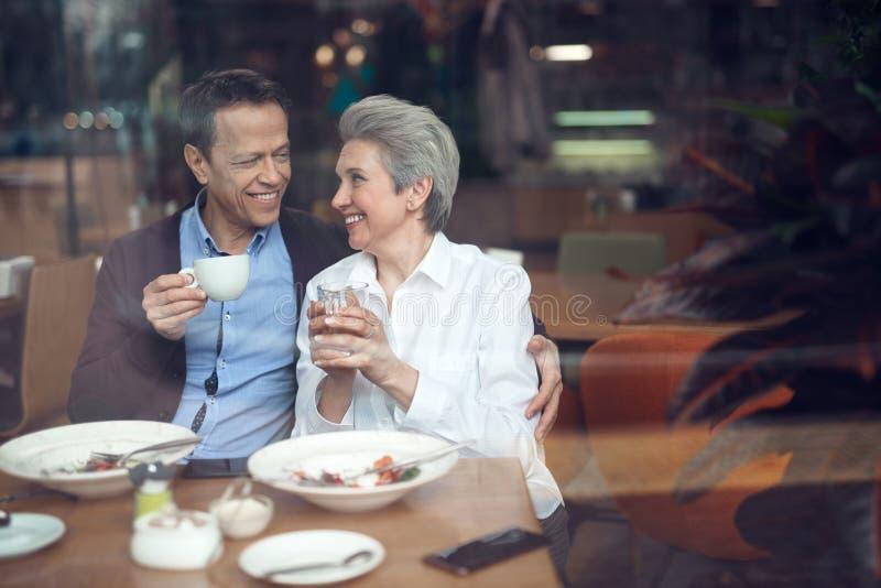 Glimlachend elegant oud paar gelukkig om in koffie samen te komen stock afbeelding