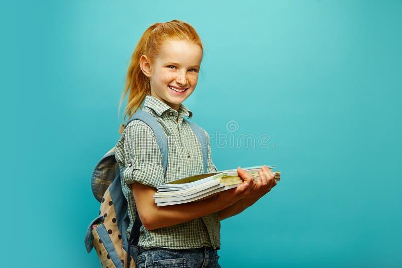 Glimlachend en mooi meisje met rood haar, die rugzak dragen, die notitieboekje met handboeken, op blauw houden student royalty-vrije stock fotografie