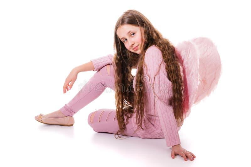 Glimlachend engelenmeisje in roze slijtage en met roze vleugels Isolatie op een wit royalty-vrije stock afbeeldingen