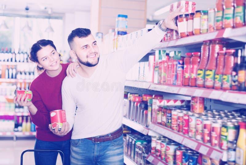 Glimlachend familiepaar het kopen ingeblikt voedsel stock afbeelding