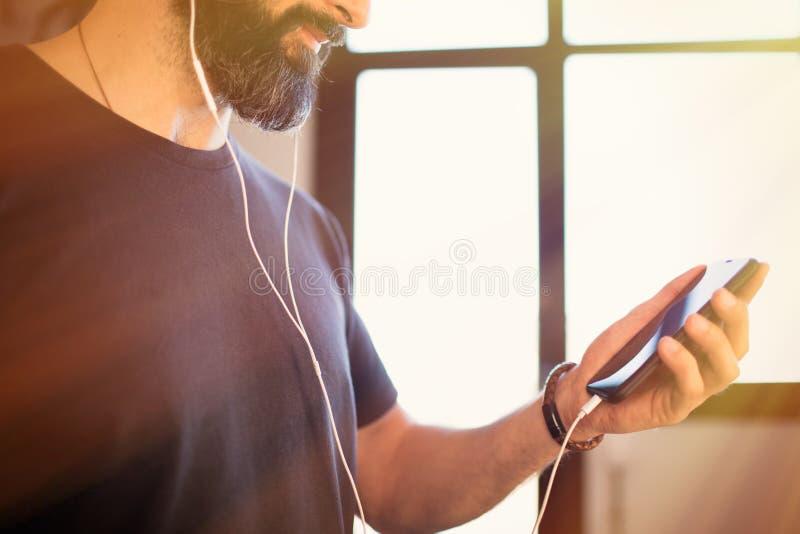 Glimlachend gebaarde kerel die toevallige grijze t-shirt het luisteren muziek in oortelefoons dragen, die sociale netwerken contr stock foto