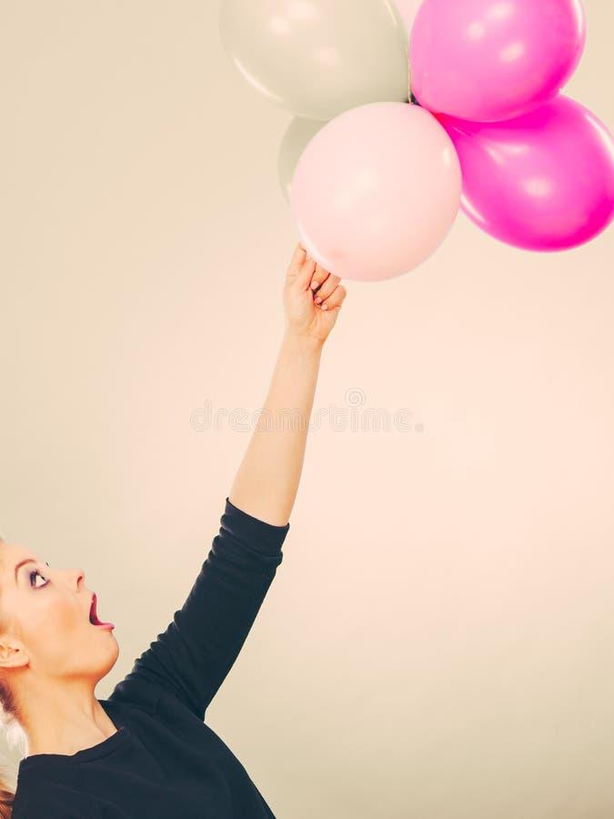 Glimlachend gek meisje die pret met ballons hebben stock afbeelding