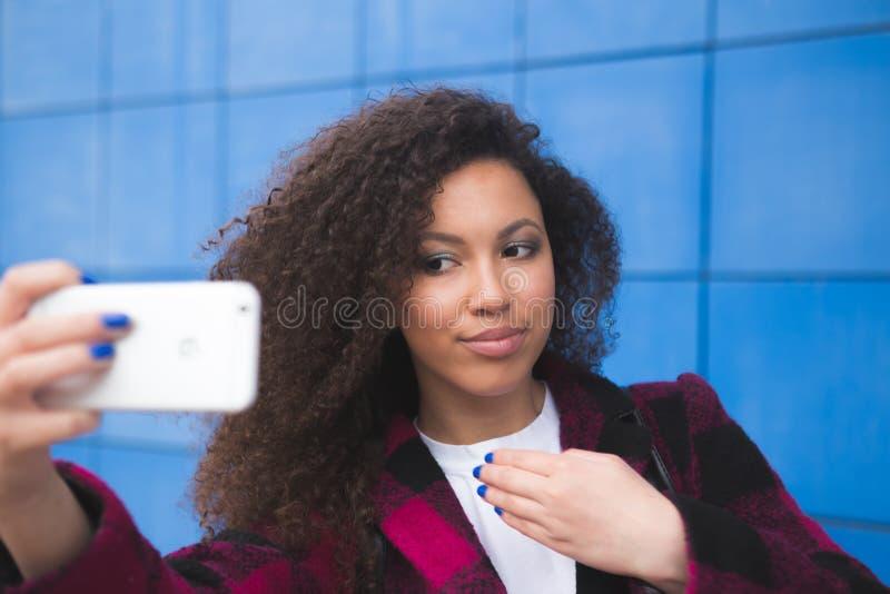 Glimlachend gelukkig jong Afrikaans Amerikaans meisje die selfie op smartphone op blauwe achtergrond nemen Technologisch concept royalty-vrije stock foto