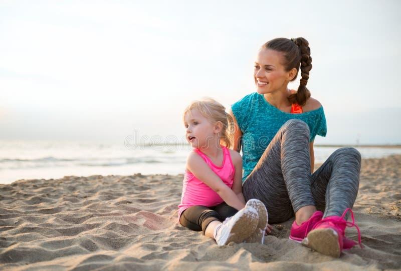 Glimlachend, geschikte moederzitting naast jonge dochter op het zand stock foto's