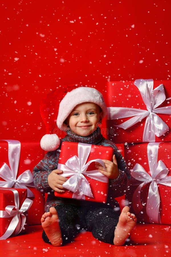 Glimlachend grappig kind in gift van de holdingskerstmis van de Kerstman de rode hoed ter beschikking Kerstmistak en klokken stock fotografie