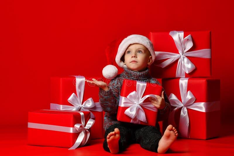Glimlachend grappig kind in gift van de holdingskerstmis van de Kerstman de rode hoed ter beschikking Kerstmistak en klokken royalty-vrije stock afbeeldingen