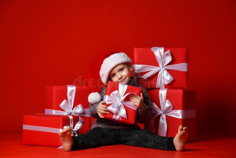 Glimlachend grappig kind in gift van de holdingskerstmis van de Kerstman de rode hoed ter beschikking Kerstmistak en klokken royalty-vrije stock foto