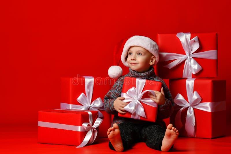 Glimlachend grappig kind in gift van de holdingskerstmis van de Kerstman de rode hoed ter beschikking Kerstmistak en klokken royalty-vrije stock fotografie