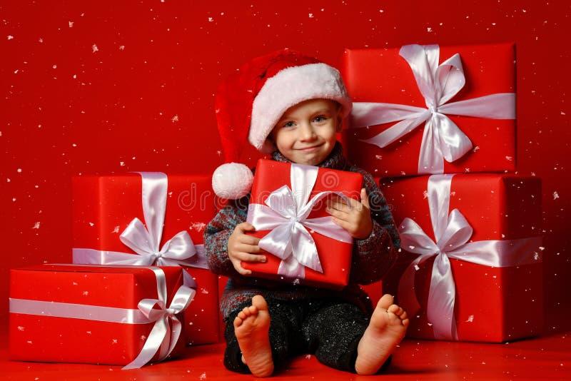 Glimlachend grappig kind in gift van de holdingskerstmis van de Kerstman de rode hoed ter beschikking Kerstmistak en klokken stock foto