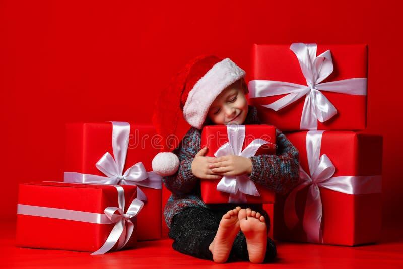 Glimlachend grappig kind in gift van de holdingskerstmis van de Kerstman de rode hoed ter beschikking Kerstmistak en klokken stock afbeeldingen