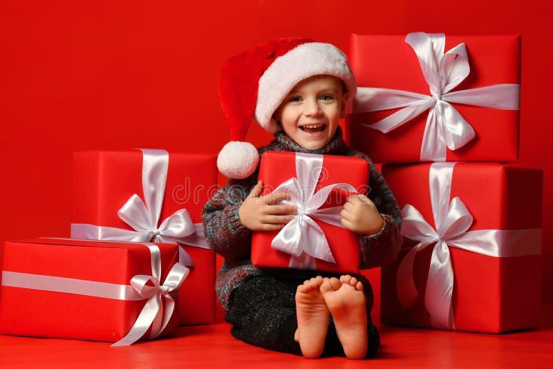 Glimlachend grappig kind in gift van de holdingskerstmis van de Kerstman de rode hoed ter beschikking Kerstmistak en klokken stock foto's