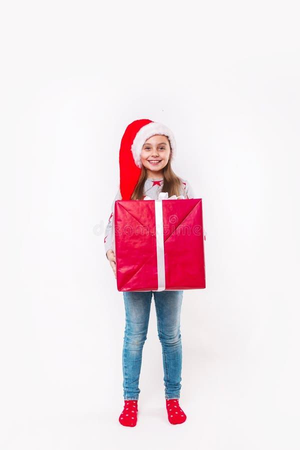 Glimlachend grappig kind in gift van de holdingskerstmis van de Kerstman de rode hoed ter beschikking Kerstmistak en klokken royalty-vrije stock foto's
