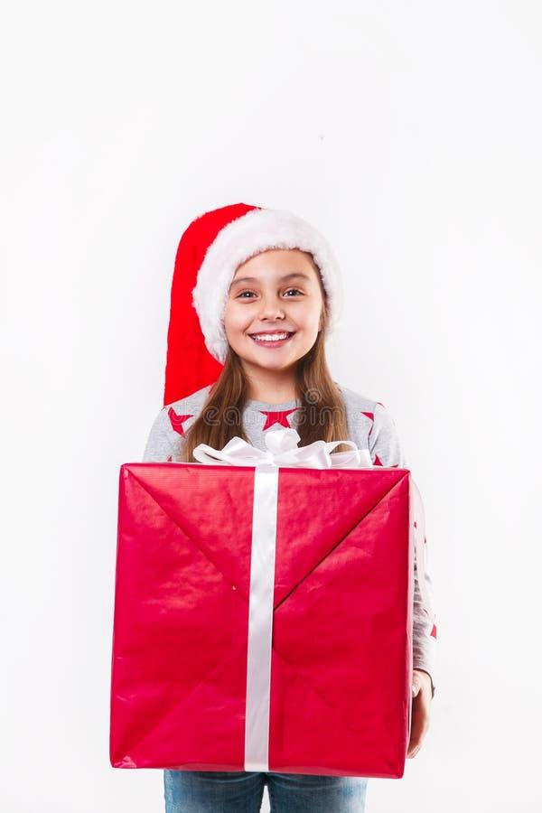 Glimlachend grappig kind in gift van de holdingskerstmis van de Kerstman de rode hoed ter beschikking Kerstmistak en klokken stock afbeelding