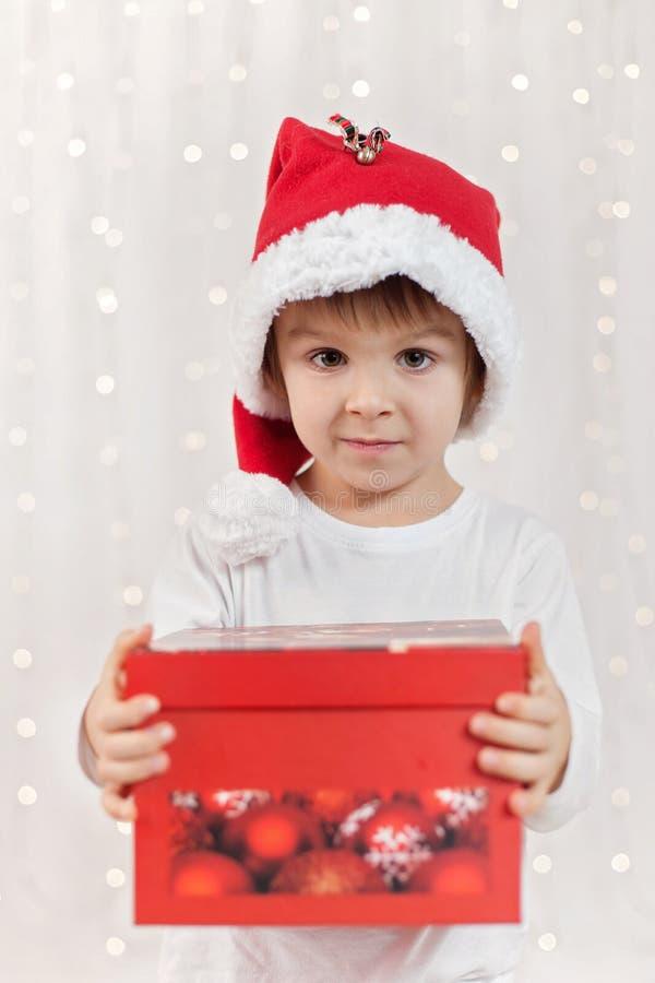 Glimlachend grappig kind in gift van de holdingskerstmis van de Kerstman de rode hoed in h stock afbeelding