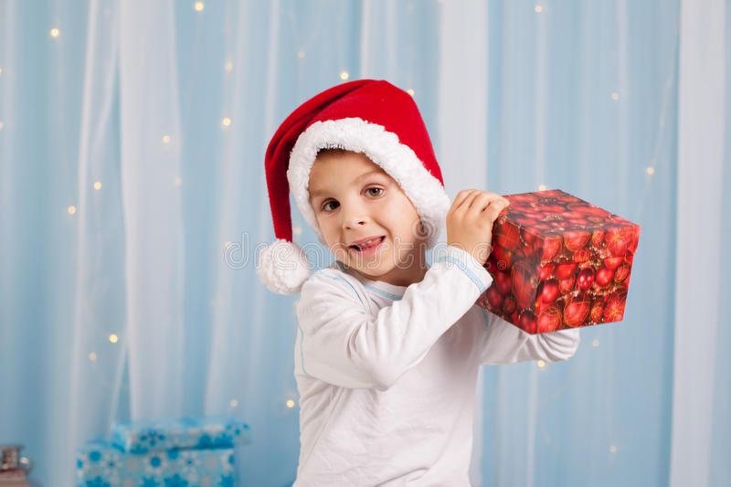 Glimlachend grappig kind in gift van de holdingskerstmis van de Kerstman de rode hoed in h royalty-vrije stock afbeelding