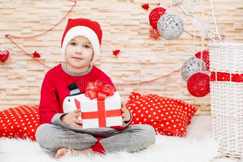 Glimlachend grappig kind in Kerstman rode hoed stock afbeeldingen