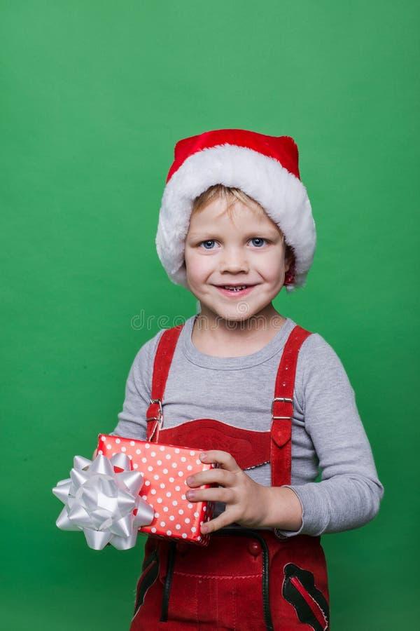 Glimlachend grappig kind in Kerstman rode hoed De gift van holdingskerstmis ter beschikking Kerstmistak en klokken stock afbeelding