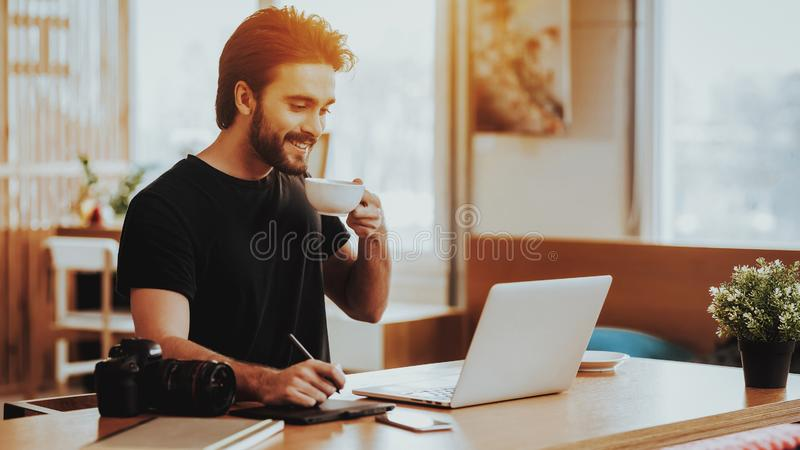 Glimlachend Guy Drinks Tea While Working op Laptop stock fotografie