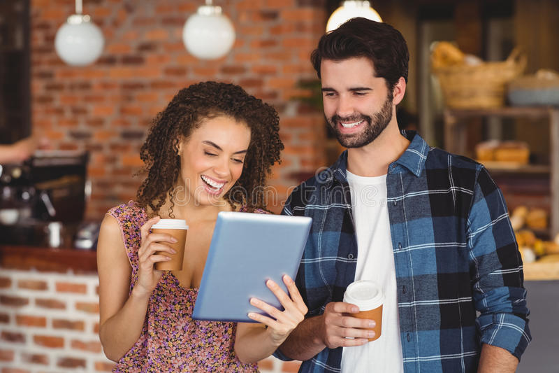 Glimlachend hipster paar met meeneemkoppen die tablet gebruiken stock foto