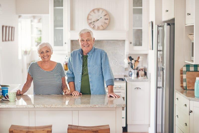 Glimlachend hoger paar die bij hun keukenteller zich thuis bevinden stock afbeeldingen